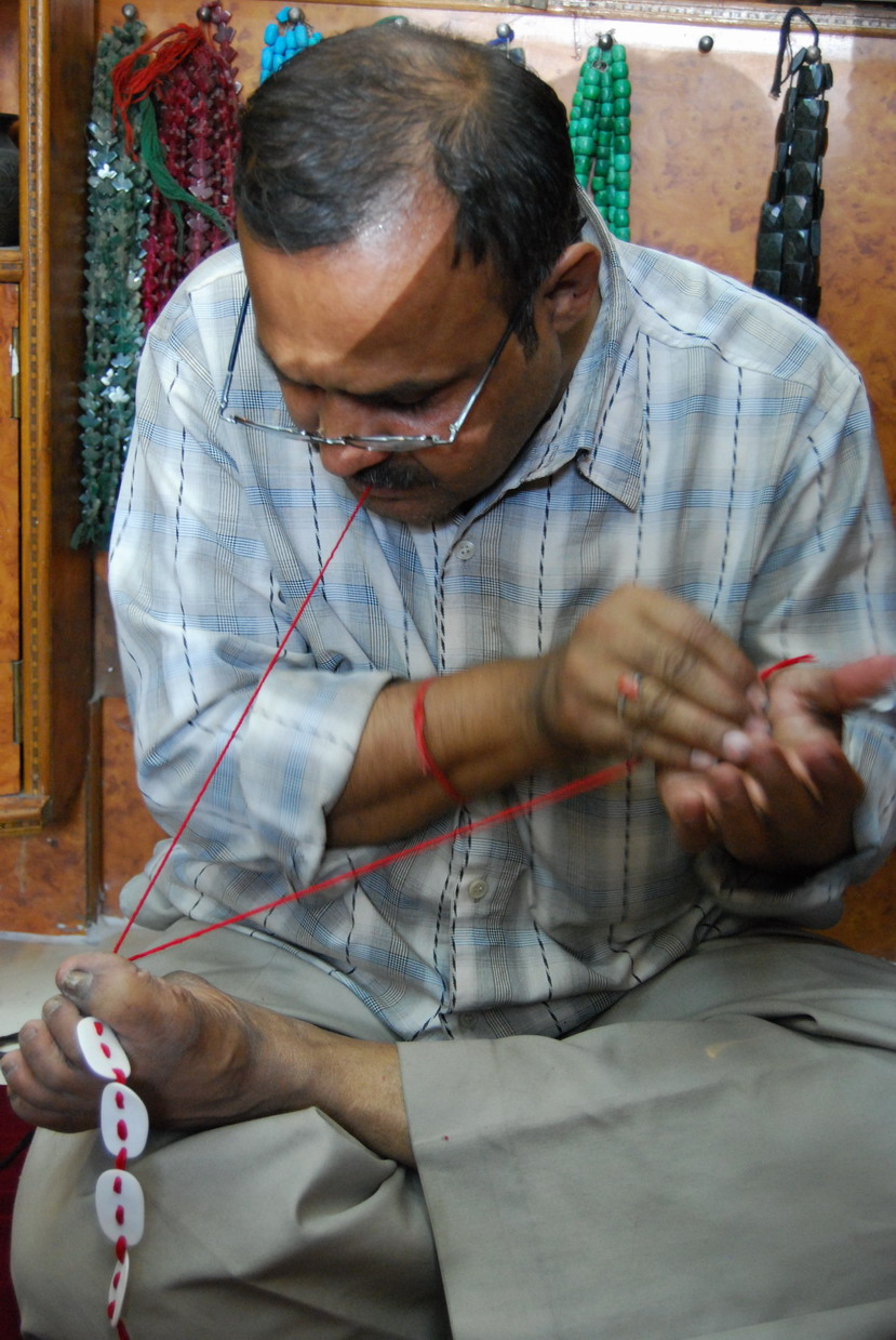 Anil Kumar threading Sandra Bowkett's necklace